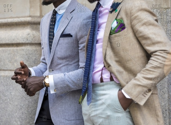 Two men wearing suits, ties and pastel shirts with contrast collar