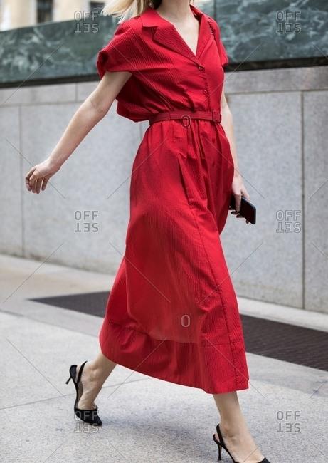 Woman striding by wearing scarlet long button up dress with belt