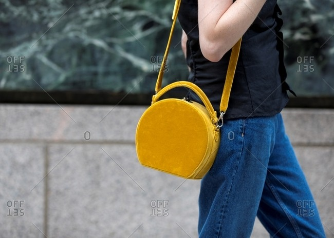 Woman carrying round mustard handbag wearing blue jeans