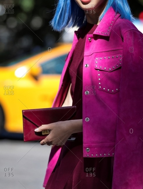 Woman with blue hair wearing magenta suede jacket with studs carrying red leather clutch
