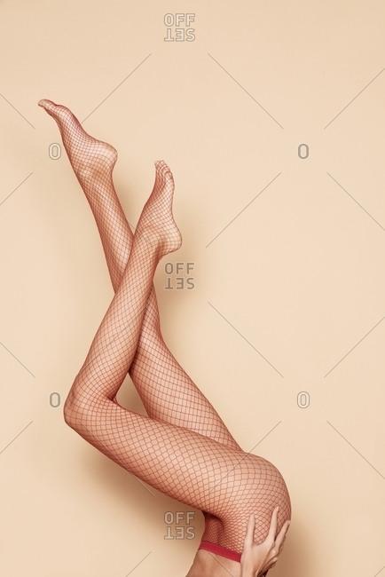 Studio shot of woman's legs wearing fishnet tights