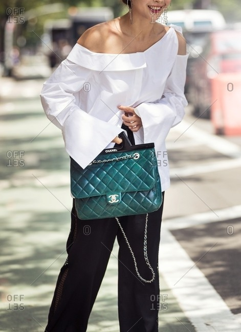 New York - March 16, 2018: Tall woman holding designer handbag on sidewalk Tall woman holding designer handbag on sidewalk