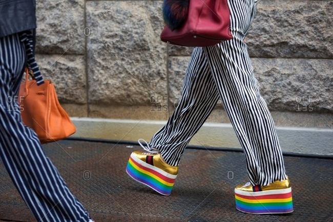 New York - March 16, 2018: Lower half view of two people walking in striped pants and flashy platform shoes