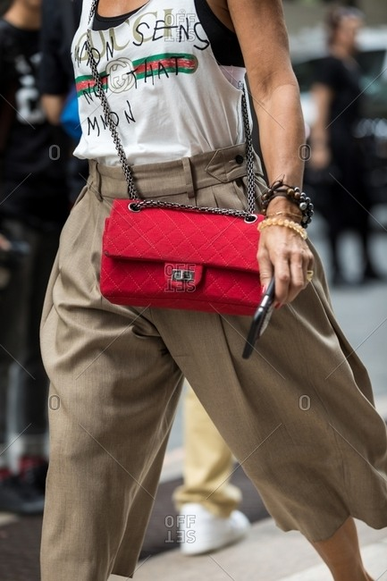 New York - March 16, 2018: Woman walking with phone in baggy capris and quilted designer purse