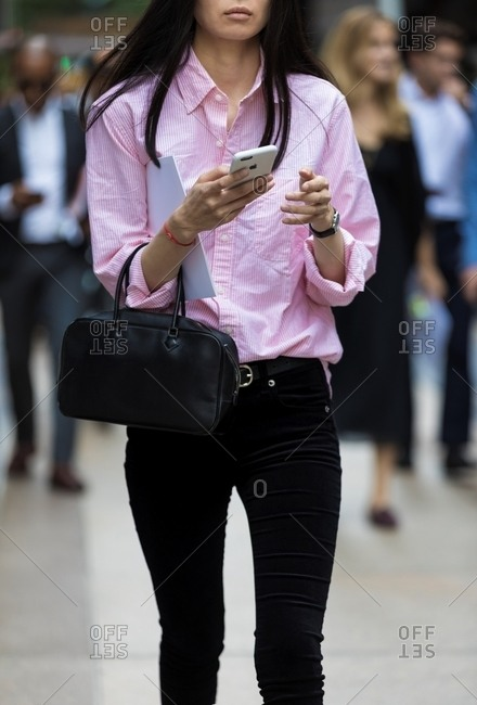 New York - March 16, 2018: Woman checking phone and walking in the city