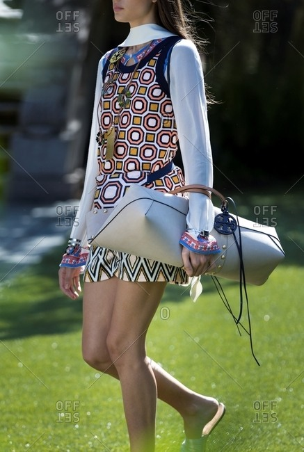 New York - March 16, 2018: Model wearing retro miniskirt carrying oversized purse through park