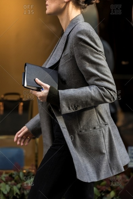 London - March 16, 2018: Woman walking with leather notebook in stylish office wear