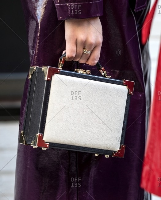London - March 16, 2018: Close-up of hand holding box purse next to leather jacket