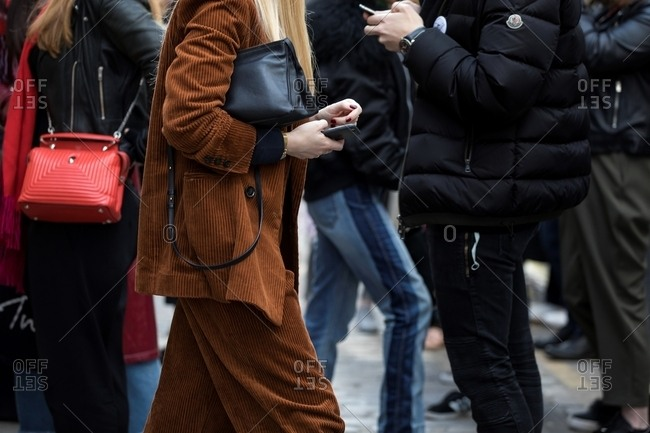 London - March 16, 2018: Woman in croupy suit checking phone in crowd