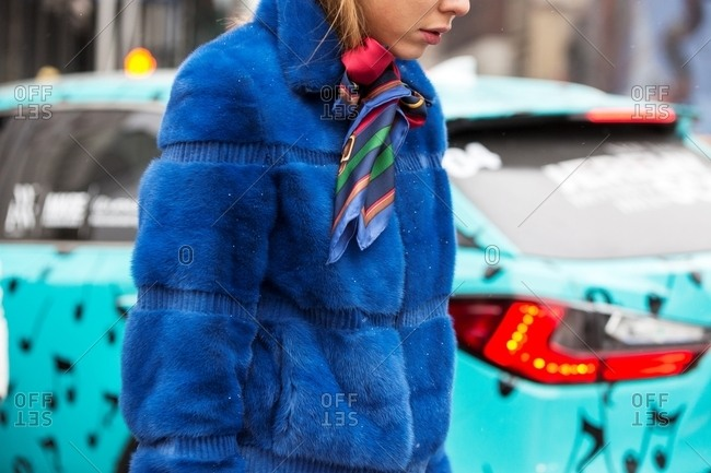 New York, USA - February 29, 2016: Woman walking in the snow wearing blue fleecy coat and silk neck scarf