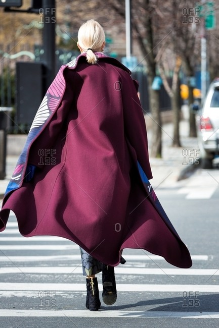 New York, USA - February 29, 2016: Rearview of woman wearing plum colored coat with flower print lining