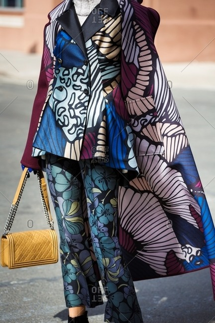 New York, USA - February 29, 2016: Woman wearing flower printed silk suit carrying yellow leather handbag