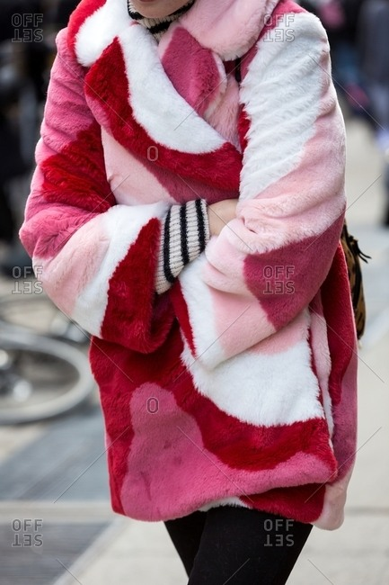 New York, USA - February 29, 2016: Woman huddles against cold in fluffy pink coat in shades of pink