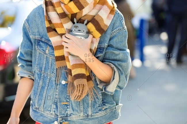 Paris, France - October 10, 2015: Woman wearing denim jacket and stripy scarf clutching phone with Totoro case