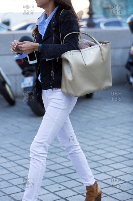 Paris, France - October 10, 2015: Woman wearing suede biker jacket carrying large Lacoste tote bag