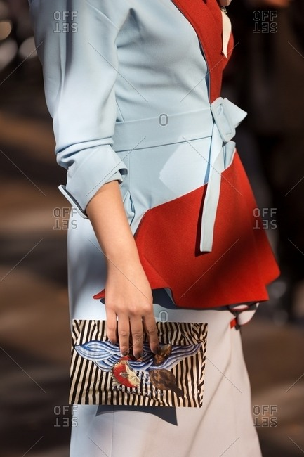 Paris, France - October 10, 2015: Woman wearing sky blue belted dress with red lining holding tiny stripy clutch with angry fish motif