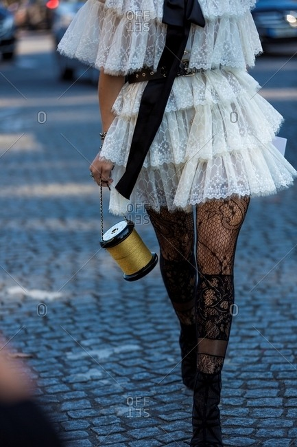 Paris, France - October 10, 2015: Woman wearing short lace dress and stockings carrying Chanel Thread Spool Clutch
