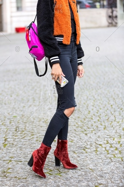 Paris, France - October 10, 2015: Woman wearing red suede ankle booties with ripped jeans and fluffy bomber jacket