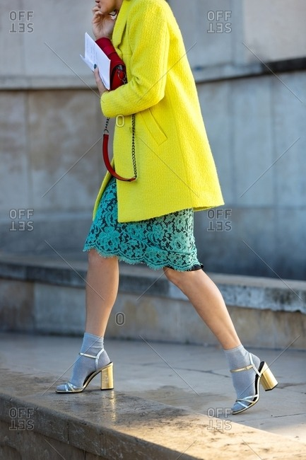 Paris, France - October 10, 2015: Woman wearing acid yellow coat and metallic strappy heels