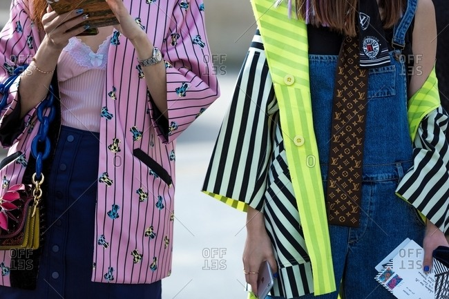 Paris, France - October 10, 2015: Pair of women wearing brightly colored striped kimono style jackets