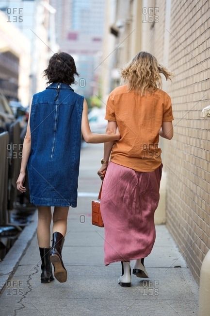New York, USA - October 10, 2015: Rearview of women wearing denim dress with patent leather boots and silk skirt with shirt and two tone boots