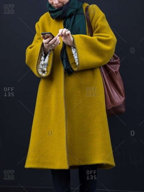 London, England - February 29, 2016: Woman checking phone wearing mustard yellow A-line coat and green scarf carrying leather shoulder bag