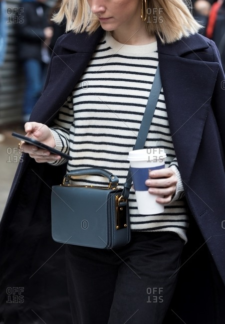 New York, USA - February 29, 2016: Woman checking phone wearing navy blue coat with Breton striped sweater and cross body bag