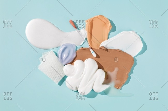 Overhead view of beauty creams and lotions smeared on background