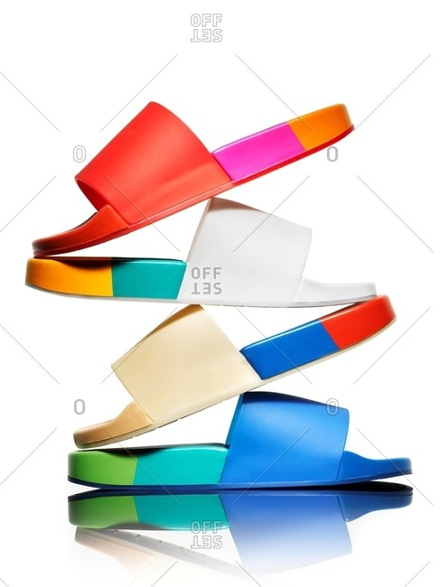 Multi colored pool sandals stacked on top of one another