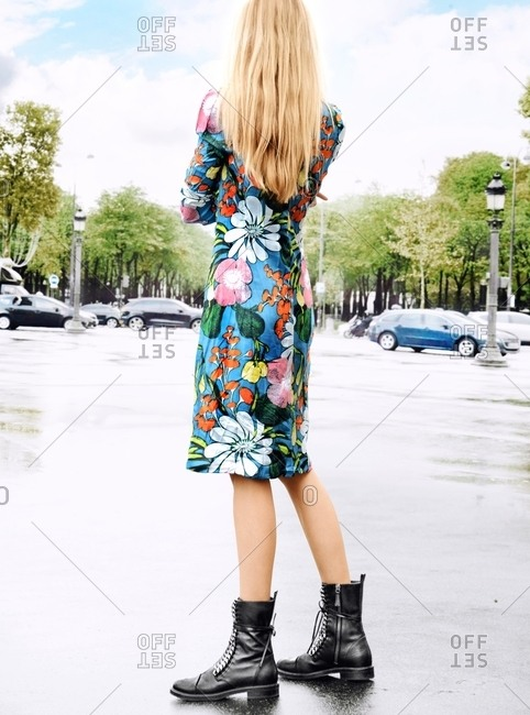 Rearview of stylish woman wearing black boots and flower dress