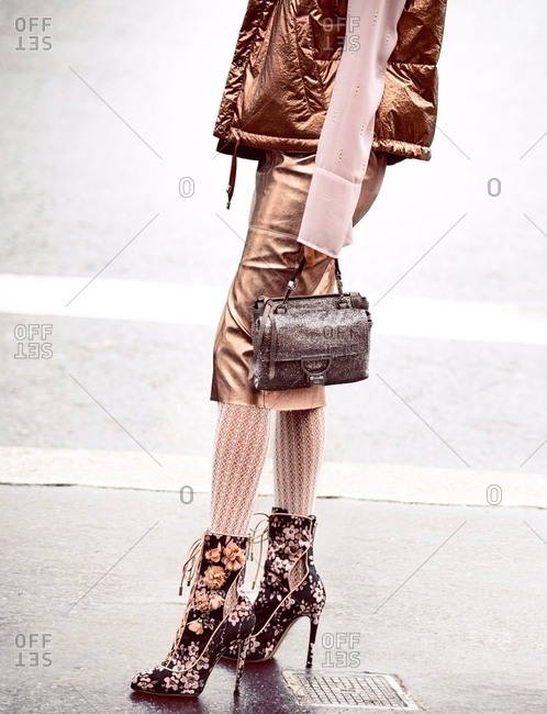 Paris, France - February 29, 2016: Woman wearing flowery boots with wickedly high heels and carrying handbag