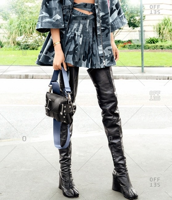 Paris, France - February 29, 2016: Woman wearing thigh high leather boots with military pattern outfit