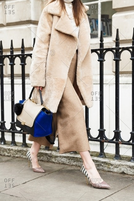 London, England - February 28, 2015: Woman wearing beige and tan outfit carrying beige and blue handbag