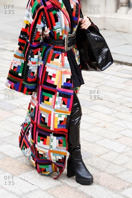 London, England - February 28, 2015: Woman wearing long patchwork coat over thigh high boots