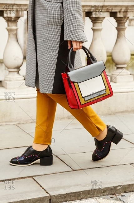 London, England - February 28, 2015: Woman wearing saffron trousers, checkered coat and Mondrian inspired handbag