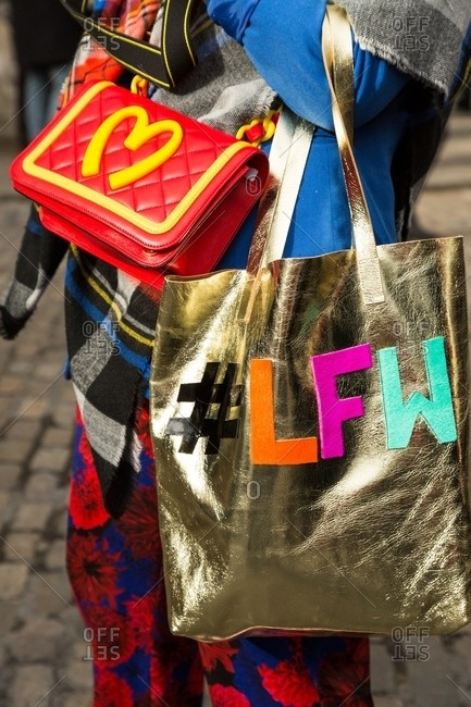London, England - March 09, 2015: Colorfully dressed woman carrying London Fashion Week tote bag and McDonalds inspired motif handbag