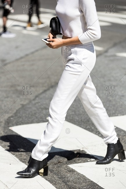 Woman striding across crosswalk wearing white crop top and white pants