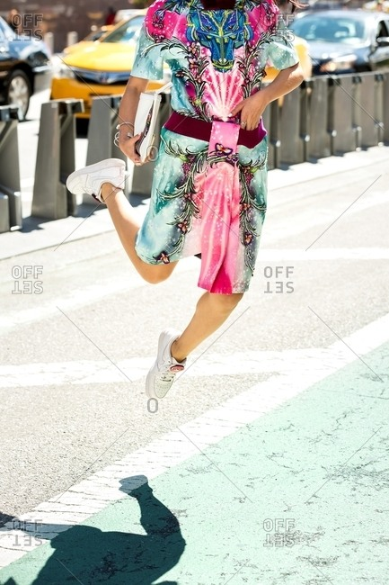 New York, USA - October 20, 2015: Woman jumping in the air wearing colorful print outfit with wolf motif