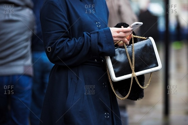 Woman using smart phone wearing navy trench coat holding black and white handbag with gold chain