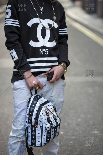London, England - February 29, 2016: Man wearing Chanel No. 5 sweatshirt carrying leather back pack