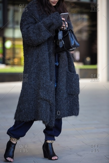 London, England - February 29, 2016: Woman in all black using smart phone wearing huge wooly coat and leather handbag