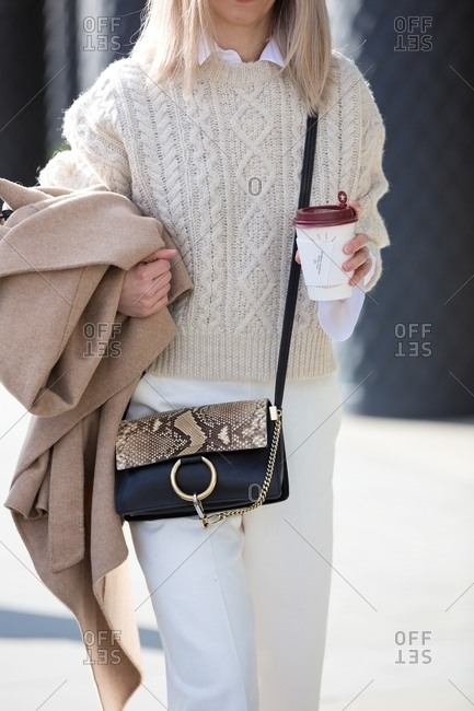 London, England - February 29, 2016: Woman carrying coffee wearing all white with snakeskin handbag