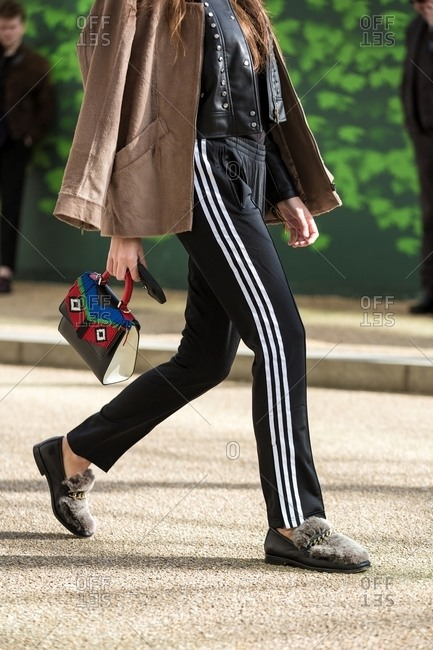 London, England - February 29, 2016: Woman striding out wearing adidas training pants and furry shoes carrying frilly handbag