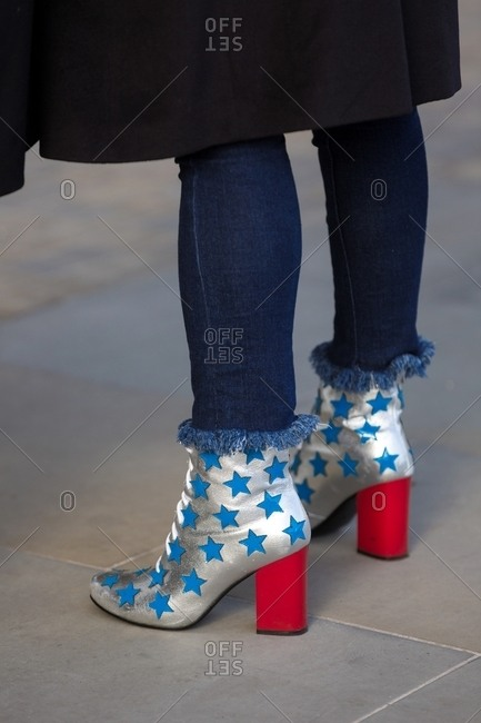 London, England - February 29, 2016: Woman wearing silver ankle boots decorated with stars and red heels