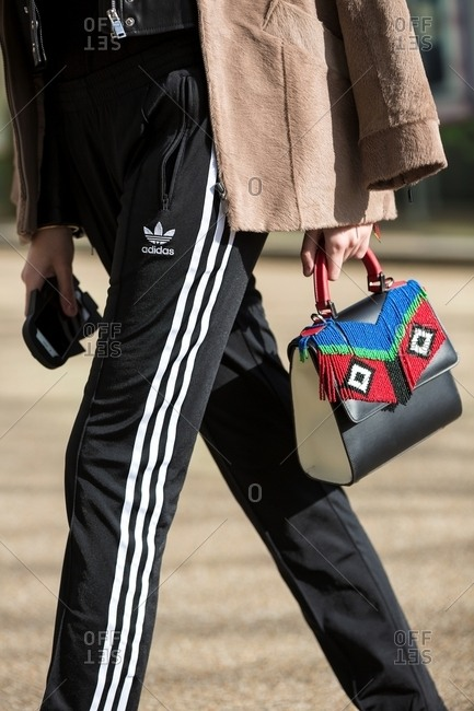 London, England - February 29, 2016: Woman wearing adidas training pants carrying frilly beaded handbag