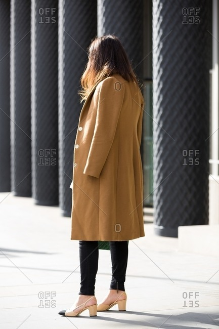London, England - February 29, 2016: Rearview of woman wearing camel coat over shoulders