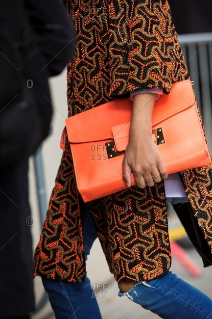 London, England - February 29, 2016: Woman holding large orange clutch wearing embroidered coat