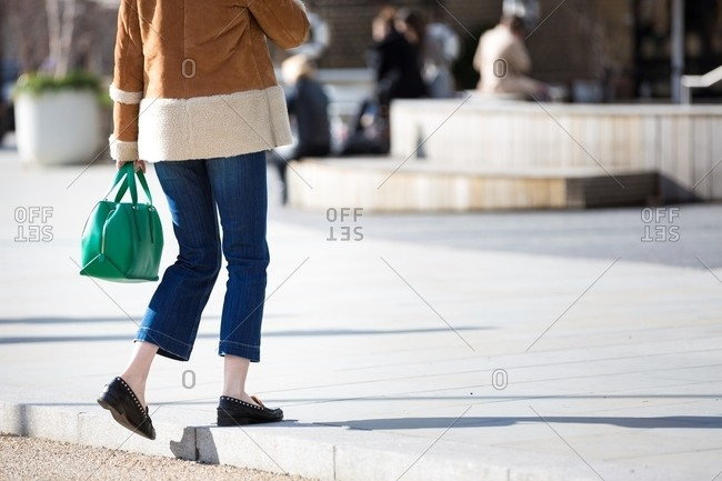 Woman stepping up onto curb wearing jeans and carrying emerald green handbag