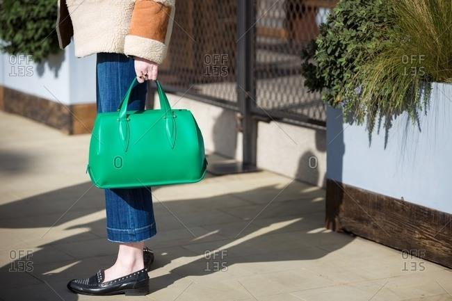 Woman carrying emerald green handbag and wearing studded loafers