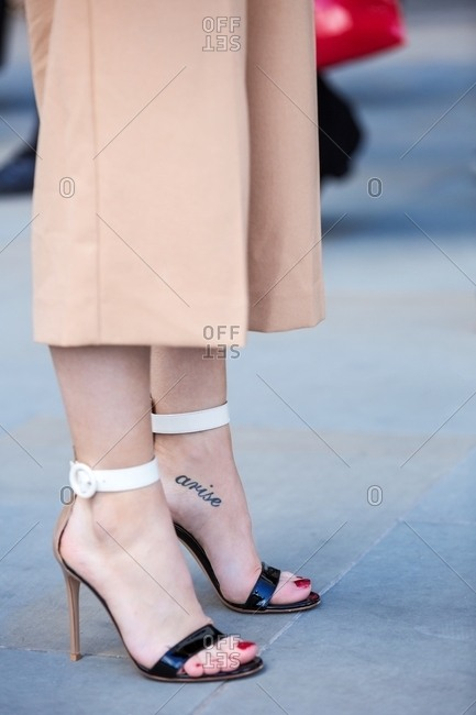 Woman in high heels with tattoo across arch of foot